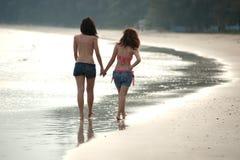 Твиновская азиатская женщина гуляя на пляж. Стоковые Изображения RF