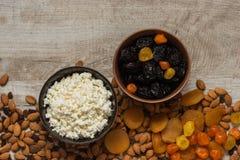 Творог в белой плите и черносливы в коричневой плите Черносливы, высушенные абрикосы, высушенные мандарины и миндалины на свете w Стоковая Фотография