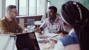 Творческая встреча команды дела в современном офисе Смешанная группа лицо одной расы молодые люди обсуждая start-up идеи, смеясь  видеоматериал