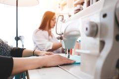 Творческая женщина dressmaker работая с тканью на швейной машине Белошвейка 2 в конструкторском бюро делая новую концепцию одежды стоковые фотографии rf
