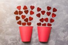 Творческая карточка валентинок 2 половина бумажного стаканчика заполняют вверх сердцами бумаг красного цвета, минимальной концепц Стоковое Изображение