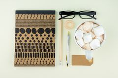 Творческая квартира кладет фото стола места для работы с eyeglasses, ручку, карандаш и тетрадь, минимальный стиль на cream предпо Стоковая Фотография