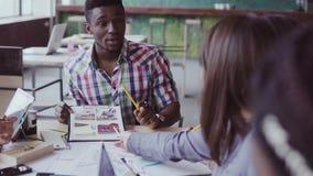 Творческая команда архитекторов встречая в современном офисе Смешанная группа лицо одной расы молодые люди обсуждая start-up идеи сток-видео