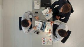 Творческая команда показывая диаграммы при компьютеры ПК компьтер-книжки и таблетки сидя на таблице в офисе Взгляд сверху Стоковые Изображения RF