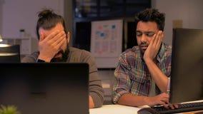 Творческая команда при компьютер работая поздно на офисе сток-видео
