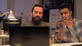 Творческая команда при компьютер работая поздно на офисе акции видеоматериалы