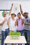 Творческая команда дела держа электрическую лампочку идеи в встрече Стоковое Изображение