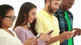 Творческая команда дела используя их телефоны в ряд акции видеоматериалы
