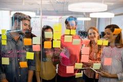 Творческая команда дела смотря липкие примечания на стеклянном окне в офисе Стоковое Изображение RF