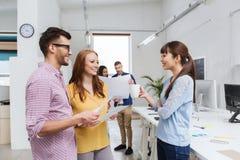 Творческая команда на перерыве на чашку кофе говоря на офисе Стоковое фото RF