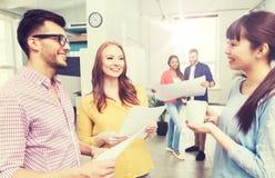 Творческая команда на перерыве на чашку кофе говоря на офисе Стоковое Фото