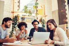 Творческая команда сидя на кафе и смотря компьтер-книжку Стоковые Изображения RF