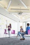 Творческая коммерсантка давая представление к коллегам в офисе Стоковые Фотографии RF