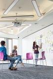 Творческая коммерсантка давая представление к коллегам в офисе Стоковое фото RF