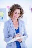 Творческая коммерсантка принимая примечание на доске сзажимом для бумаги Стоковые Изображения
