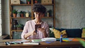 Творческая молодая женщина режет кусок бумаги при ножницы создавая коллаж после этого кладя ее в тетрадь и проверять видеоматериал