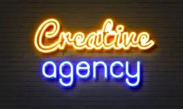 Творческая неоновая вывеска агенства на предпосылке кирпичной стены стоковое изображение