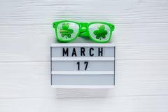 Творческая праздничная предпосылка St Patricks с календарем 17-ое марта коробки белого света и стекла потехи зеленые с shamrock стоковая фотография