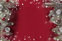Творческая рамка плана сделанная ветвей ели рождества, конусов сосны, подарков, красного украшения на красной предпосылке стоковое фото rf