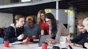 Творческая multi этническая команда обсуждая новый проект используя прибор компьютера на встрече творческих директоров внутри сток-видео