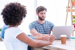 Творческие бизнесмены используя компьтер-книжку в встрече Стоковые Изображения