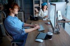 Творческие дизайнеры работая дополнительное время на компьютере для нового проекта Стоковые Фото