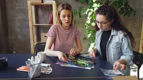 Творческие дизайнеры устанавливают фото на таблице и делят идеи пока сидящ в современном офисе творческий думать акции видеоматериалы