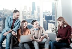 Творческие дружелюбные коллеги сидя и держа компьтер-книжки Стоковое Фото