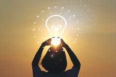 Творческие идея и концепция нововведения, электрическая лампочка удерживания руки женщины на красивой предпосылке захода солнца стоковая фотография rf