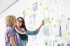 Творческие коммерсантки обсуждая над бумагами вставили на стене в офисе Стоковое Изображение RF