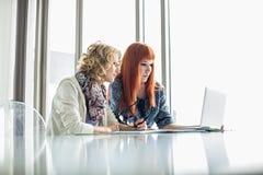 Творческие коммерсантки работая на компьтер-книжке совместно в офисе Стоковое фото RF