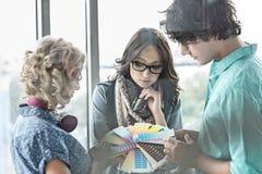 Творческие предприниматели анализируя образцы цвета в офисе Стоковое Изображение