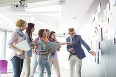 Творческие предприниматели обсуждая над документами на стене в офисе Стоковые Изображения