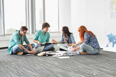Творческие предприниматели обсуждая пока сидящ на поле в офисе Стоковые Фото
