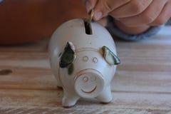 Творческие сбережения концепция, рука и копилка стоковая фотография