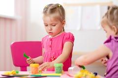 Творческие способности детей Дети ваяют от глины Милая маленькая девочка отливает в форму от пластилина на таблице в питомнике Стоковое Изображение