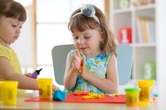 Творческие способности детей Ребенк ваяет от глины Милая маленькая девочка отливает пластилин в форму на таблице Стоковые Фото
