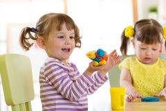 Творческие способности детей Дети ваяя от глины Милые мальчики отливают в форму от пластилина на таблице в комнате Стоковое фото RF