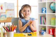 Творческие способности детей Ребенк ваяет от глины Милые прессформы маленькой девочки от пластилина на таблице Стоковая Фотография RF