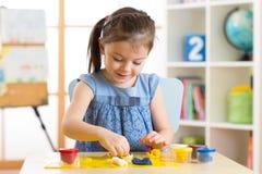 Творческие способности детей Ребенк ваяет от глины Милые прессформы маленькой девочки от пластилина на таблице Стоковые Фото