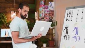 Творческий арт-директор идя в офис держа его ноутбук и смотря доску дизайна акции видеоматериалы