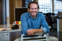 Творческий бизнесмен сидя на стуле против стола компьютера Стоковые Изображения RF