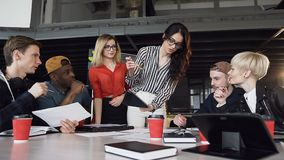 Творческий женский руководитель группы стоя близко вокруг таблицы и давая направление к молодой творческой команде на встрече на  акции видеоматериалы