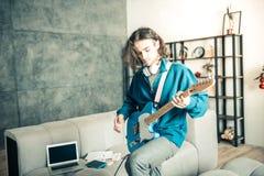 Творческий молодой музыкант будучи включанным в повторение музыки стоковая фотография rf