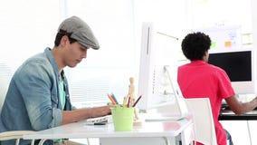 Творческий работник работая на его компьютере на столе сток-видео