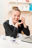 Творческий работник усмехаясь в офисе, и скомканная бумага Стоковые Фотографии RF
