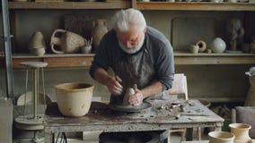 Творческий старший гончар мочит руки в шаре с водой и касающей частью глины на закручивая бросать-колесе сток-видео