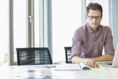 Творческий файл чтения бизнесмена на столе в офисе Стоковая Фотография