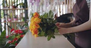 Творческий флорист девушки аранжируя пук роз в красивом составе на работе сток-видео