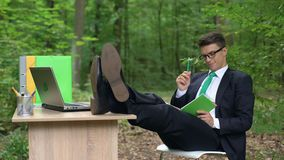 Творческий человек в костюме пробует найти идея для проекта дела, сидя в природе видеоматериал